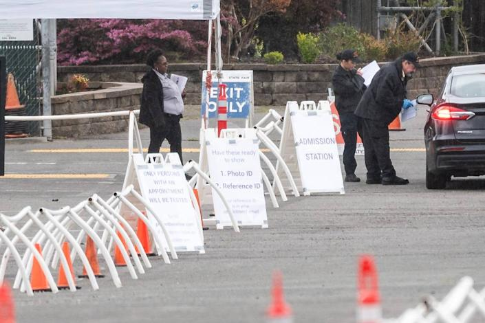 People pull their vehicles up to a checkpoint with signage for testing at CalExpo on Tuesday, March 24, 2020, in Sacramento.