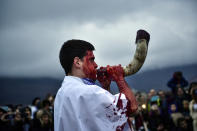 ''Momotxorro'' with his face covered with blood blood plays a horn while taking part in the carnival, in Alsasua, northern Spain, Tuesday, Feb. 25, 2020. During the carnival Momotxorros, characters who seem to have been resurrected from a prehistoric ritual, come out onto the streets wearing horns and hiding their faces under headscarves, and dressed in a white sheet stained with blood. (AP Photo/Alvaro Barrientos