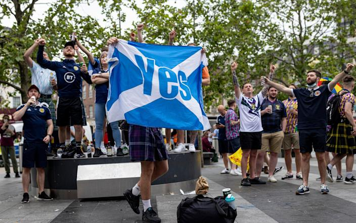 """A Scotland fan holds up the flag of Scotland with the word """"Yes"""" written across it, associated with the campaign for Scotland's independence from the United Kingdom - Rob Pinney/Getty Images Europe"""