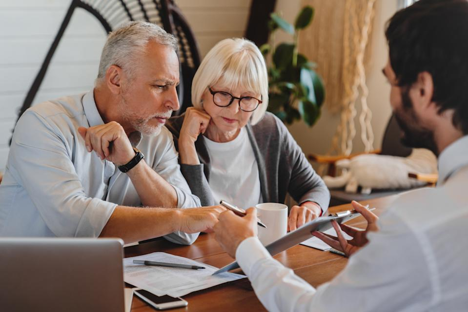 Financial advisor explaining paperwork to elderly retired couple front of desk
