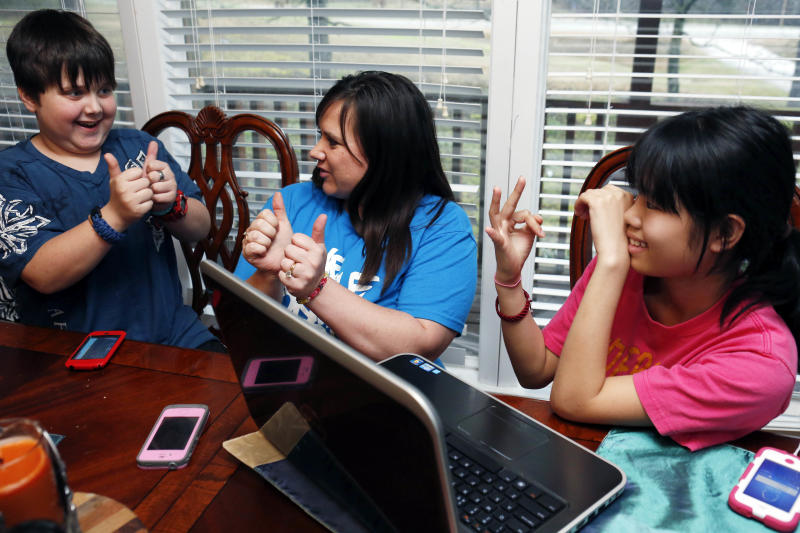 In this April 4, 2013 photograph, Colton Smith, 10, left, uses a combination of some basic Chinese and English sign languages with his mother, Niki Smith, center, to communicate with their family's newest member, 14-year-old Guan Ya, in their Rienzi, Miss., home. Although the Smiths and their three other children are using the Google Translate program to communicate almost exclusively with Guan Ya, who is deaf, the children use a variety of signs as well. The family uses iPhones, iPods and a laptop, all loaded with the program to write in either English that translates to Chinese or vice-a-versa. (AP Photo/Rogelio V. Solis)