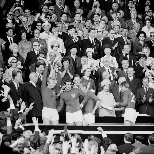 Roger Hunt receives his World Cup winners' medal from the Queen as England captain Bobby Moore holds the trophy aloft