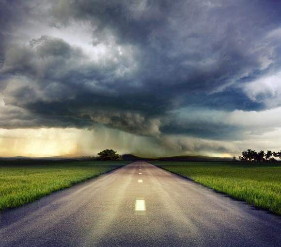 A storm on the horizon down a long road.