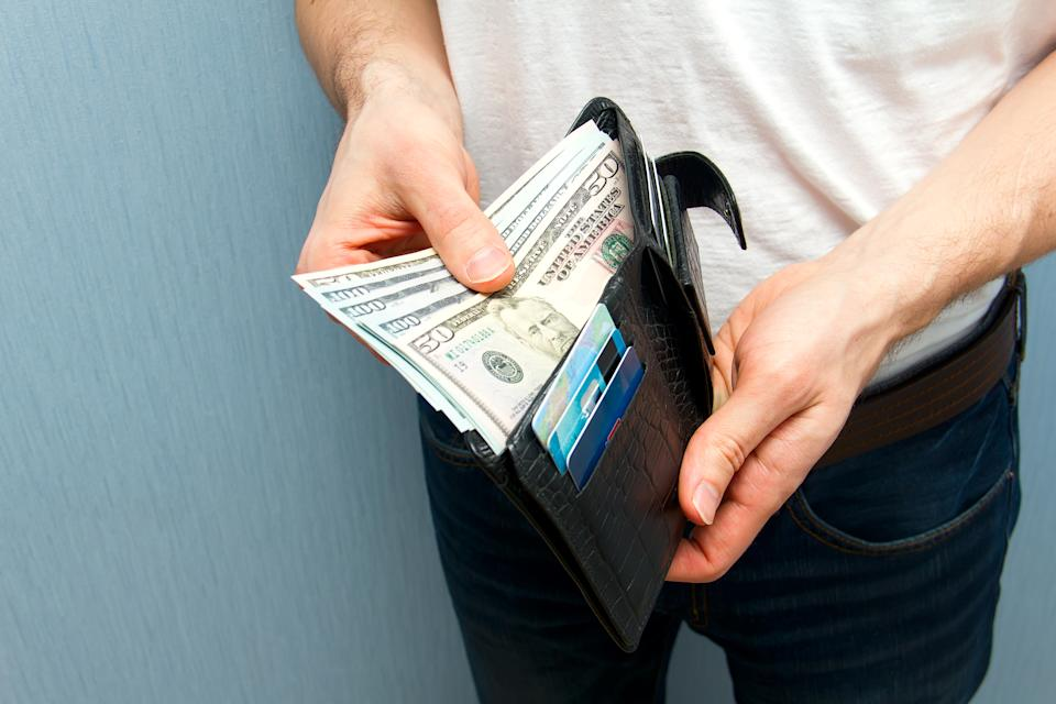 A man with a wallet full of cash in his hands