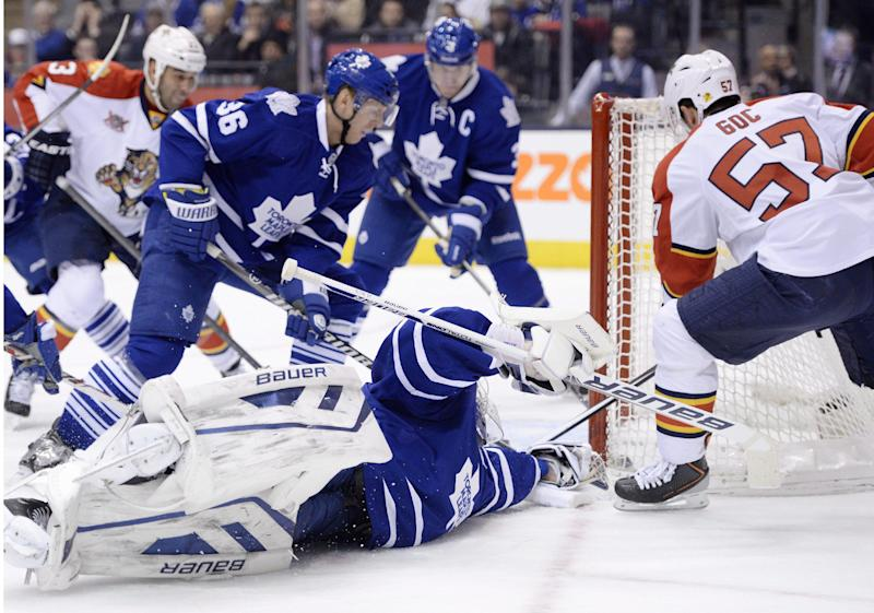Toronto Maple Leafs goalie James Reimer scrambles to make a save as Florida Panthers' Marcel Goc, 57, looks for the loose puck and Maple Leafs' Carl Gunnarsson defends. 36, during first period NHL action in Toronto on Tuesday, Dec. 17, 2013. (AP Photo/The Canadian Press, Frank Gunn)