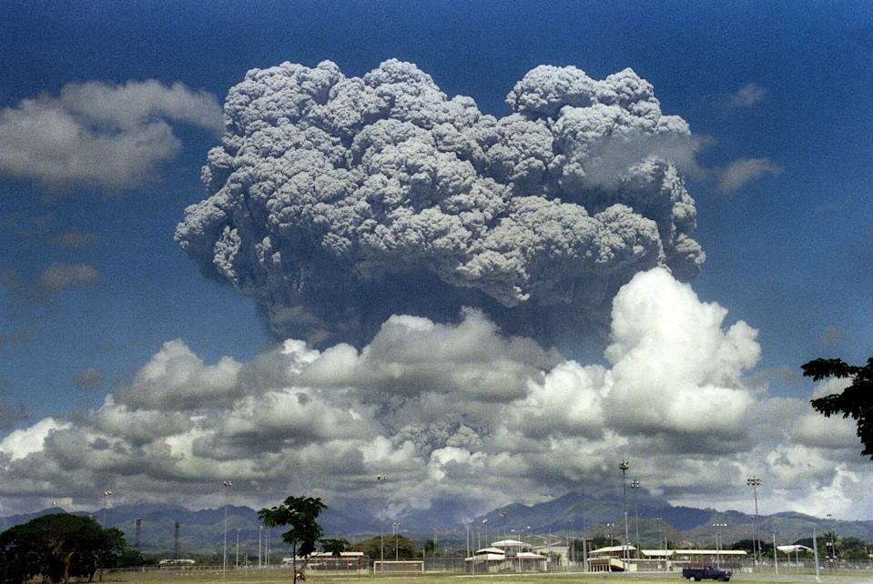 FILE PHOTO: A giant volcanic mushroom cloud explodes some 20 kilometers high from Mount Pinatubo above almost deserted US Clark Air Base, on June 12, 1991 followed by another more powerful explosion.  (Photo: ARLAN NAEG/AFP via Getty Images)