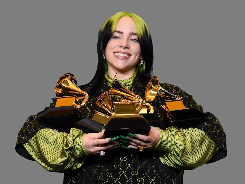 """Billie Eilish, as singer-songwriter, poses in the press room with the awards for best album and best pop vocal album for """"We All Fall Asleep, Where Do We Go?"""", best song and record for """"Bad Guy"""" and best new artist at the 62nd annual Grammy Awards at the Staples Center, Los Angeles, graphic element on gray"""