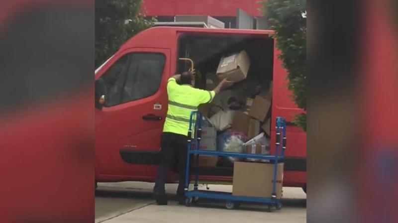 The worker was seen lobbing package after package from a tray into the van just outside Arena post office in Melbourne. Source: Facebook / Glenn Burr