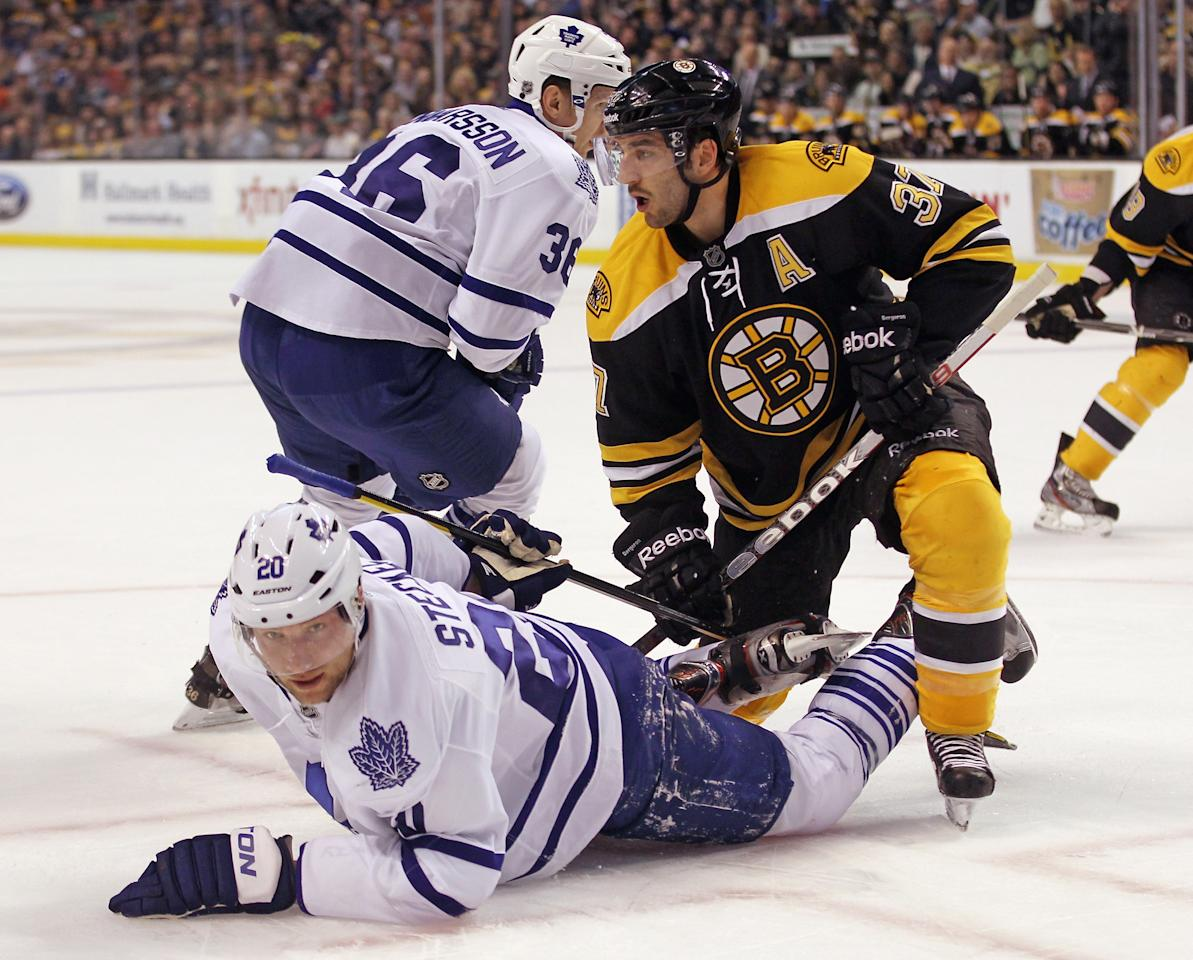 BOSTON, MA - MARCH 19: Patrice Bergeron #37 of the Boston Bruins knocks down David Steckel #20 of the Toronto Maple Leafs off the faceoff at the TD Garden on March 19, 2012 in Boston, Massachusetts.  (Photo by Bruce Bennett/Getty Images)
