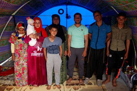 Displaced Iraqi woman Farah Taha, 60, poses for a photograph with her three sons, her daughter-in-law, her six-month-old grandchild as well as the brother and sister of her daughter-in-law, in the family tent in Hammam al-Alil camp south of Mosul, Iraq March 29, 2017. Taha says she has been unable to find any work to support her family since fleeing their Mosul home. REUTERS/Suhaib Salem