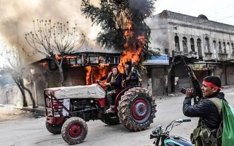 A Turkish-backed Syrian rebel drives past a burning shop in the city of Afrin in northern Syria on March 18 - Credit: BULENT KILIC/AFP