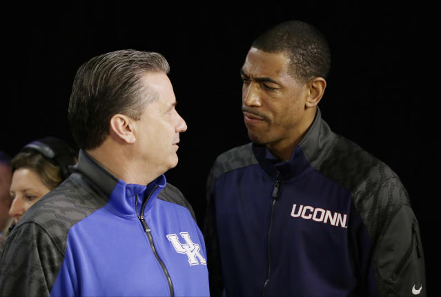 Connecticut head coach Kevin Ollie and Kentucky head coach John Calipari talk during a television interview for the NCAA Final Four tournament college basketball championship game Sunday, April 6, 2014, in Arlington, Texas. Connecticut plays Kentucky in the championship game on Monday, April 7. 2014. (AP Photo/David J. Phillip)