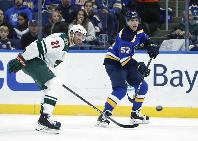 St. Louis Blues' David Perron (57) passes the puck as Minnesota Wild's Eric Fehr (21) watches during the second period of an NHL hockey game Sunday, Nov. 11, 2018, in St. Louis. (AP Photo/Jeff Roberson)