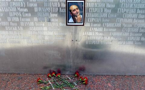 Flowers lay under a picture of Arkady Babchenko in Kiev - Credit: VASILY MAXIMOV/AFP