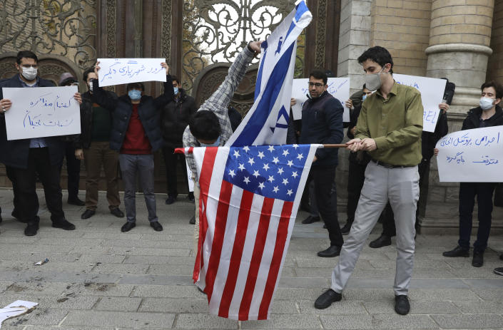 """Two protesters burn the representation of the U.S. and Israeli flags as the others hold placards condemning inspections by the UN nuclear agency (IAEA) on Iran's nuclear activities and the country's nuclear talks with world powers during a gathering in front of Iranian Foreign Ministry on Saturday, Nov. 28, 2020 in Tehran. Supreme Leader Ayatollah Ali Khamenei is calling for """"definitive punishment"""" of those behind killing of Mohsen Fakhrizadeh, the scientist linked to Tehran's disbanded military nuclear program. (AP Photo/Vahid Salemi)"""
