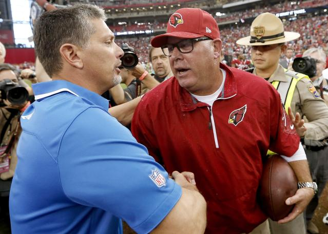 As he carries the game ball, Arizona Cardinals head coach Bruce Arians, right, shakes hands with Detroit Lions head coach Jim Schwartz after an NFL football game on Sunday, Sept. 15, 2013, in Glendale, Ariz. The Cardinals defeated the Lions 25-21. (AP Photo/Ross D. Franklin)