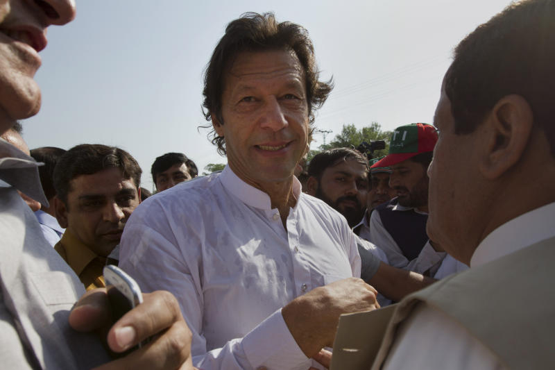 """Pakistan's ex-cricket star-turned-politician Imran Khan, center, is surrounded by his supporters as he arrives to lead what organizers are calling the """"peace march,"""" in Islamabad, Pakistan, Saturday, Oct. 6, 2012. Hundreds of Pakistanis, joined by dozens of American activists, set off Saturday on a motorcade """"march"""" to protest against U.S. drone strikes, hoping to reach a militant-riddled Afghan border region that has been the focus of many such attacks. (AP Photo)"""