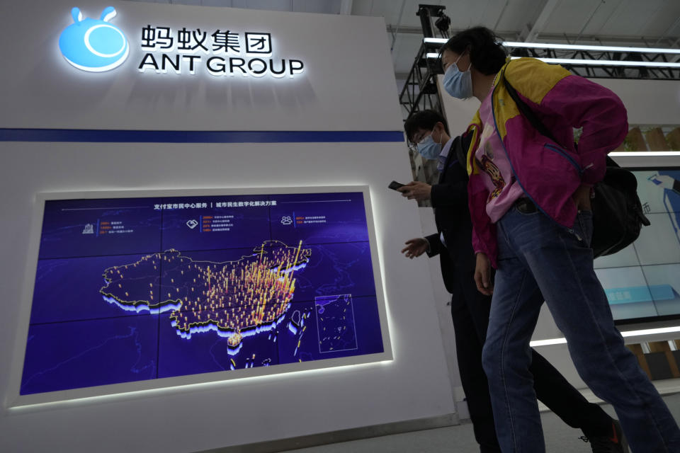 Visitors to a trade fair past by the Ant Group booth in Beijing, China, Monday, Sept. 6, 2021. China's central bank will soon have access to private credit information of hundreds of millions of users of Ant Group's online credit service, in a move signaling more regulatory oversight of the financial technology sector. (AP Photo/Ng Han Guan)