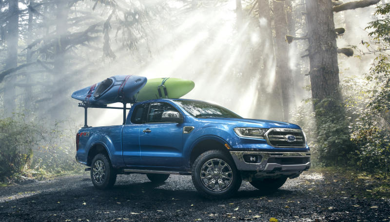 A blue 2019 Ford Ranger, a midsize pickup, is shown in a forest setting. There are two kayaks loaded on a rack in the Ranger's bed.
