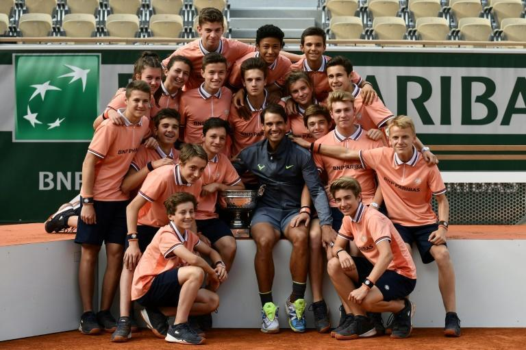 Man of the people: Rafael Nadal poses with ball boys and girls after winning the 2019 French Open