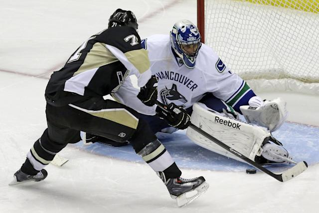 Pittsburgh Penguins' Evgeni Malkin (71) gets the game-winning goal past Vancouver Canucks goalie Roberto Luongo (1) in an overtime shootout during an NHL hockey game in Pittsburgh Saturday, Oct. 19, 2013. The Penguins won 4-3. (AP Photo/Gene J. Puskar)