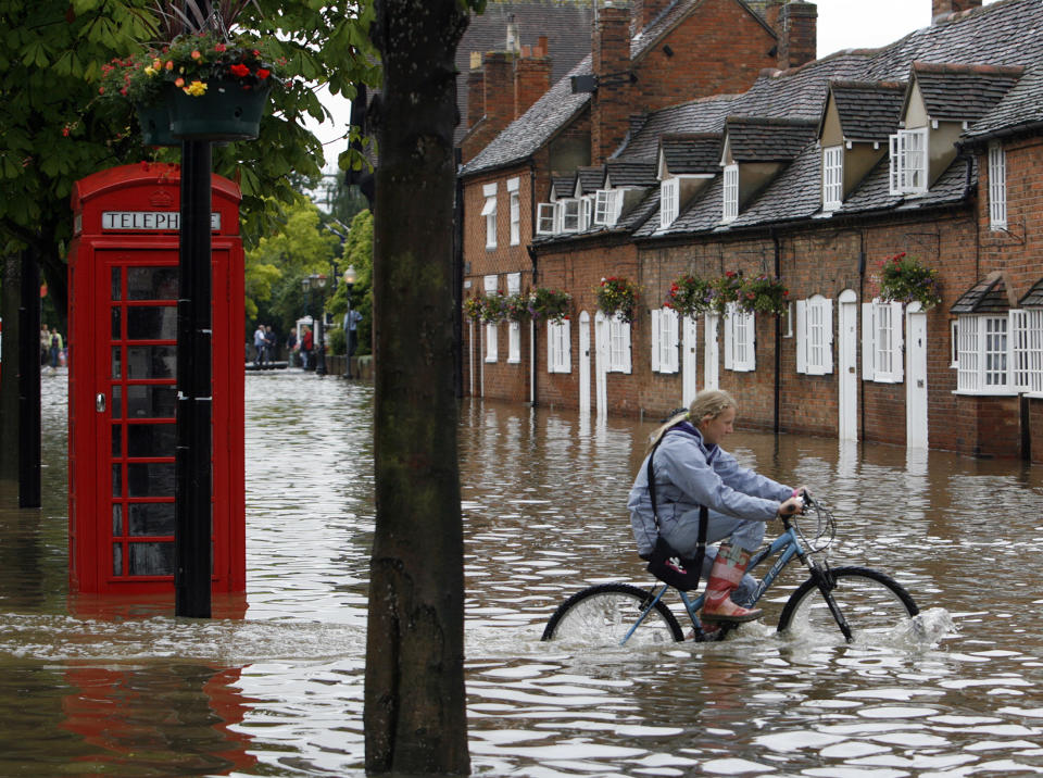 A girl cycles through flood waters in Stratford Upon-Avon, central England, July 21, 2007. Torrential rain caused flash floods and brought transport chaos, the Highways Agency said on Saturday. As many as 2,000 people had to be taken to emergency centres in the Cotswolds, one of England's most picturesque regions.    REUTERS/Darren Staples  (BRITAIN)