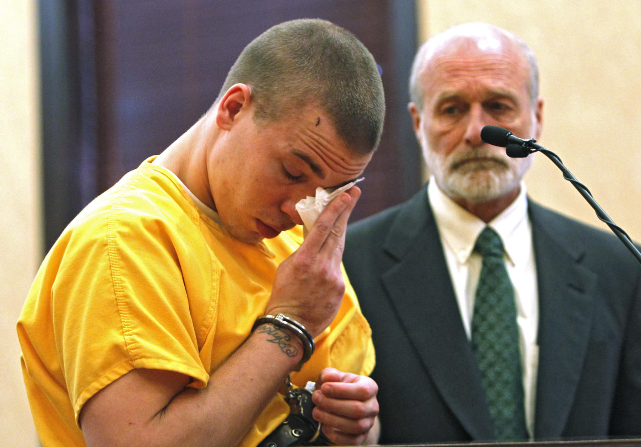 Ryan Dougherty wipes tears from his eyes in district court in Walsenburg, Colo., on Monday, April 30, 2012, where he was sentenced to 18 years in prison on charges stemming from he and his siblings shootout and capture in Colorado. Attorney Michael Emmons looks on at right. All three siblings were sentenced on Monday. The three are accused of shooting at a police officer and staging a daring bank robbery in a cross-country crime spree that included Georgia and Florida. The manhunt for them ended after an Aug. 10 freeway chase and shootout with police in southern Colorado. (AP Photo/Ed Andrieski, Pool)