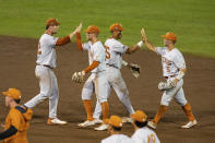 Texas Zach Zubia (52) and Eric Kennedy (30), and Camryn Williams (55) and Mike Antico (5) give each other a high five celebrating their win over Virginia during a baseball game in the College World Series Thursday, June 24, 2021, at TD Ameritrade Park in Omaha, Neb. (AP Photo/John Peterson)