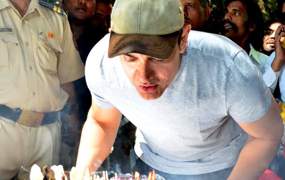 Aamir celebrates his 47th birthday, as he cuts the cake with his fans.