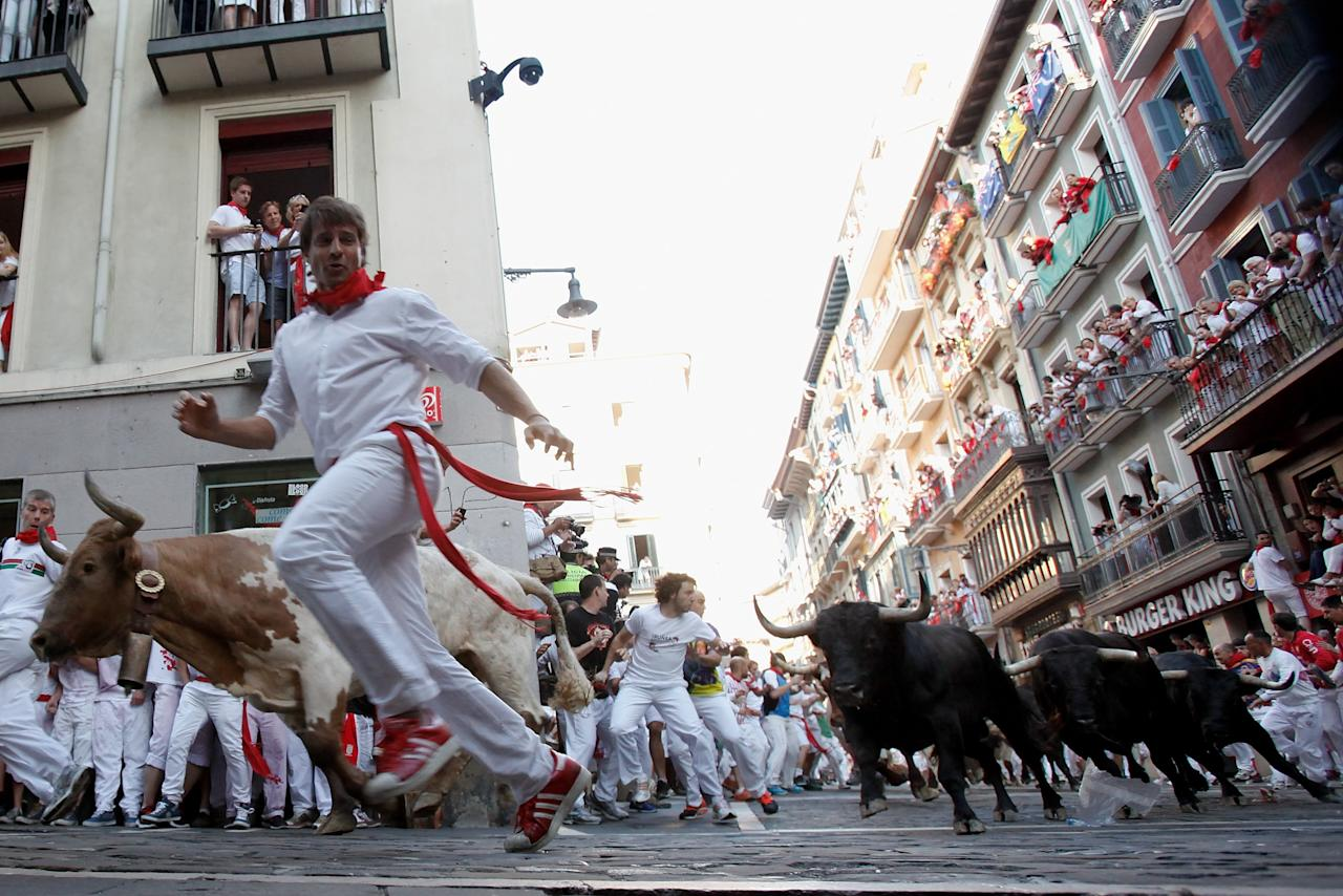 PAMPLONA, SPAIN - JULY 08: Revellers run with Dolores Aguirre's ranch fighting bulls at Curva Estafeta during the third day of the San Fermin Running Of The Bulls festival, on July 8, 2013 in Pamplona, Spain. The annual Fiesta de San Fermin, made famous by the 1926 novel of US writer Ernest Hemmingway 'The Sun Also Rises', involves the running of the bulls through the historic heart of Pamplona for nine days from July 6-14. (Photo by Pablo Blazquez Dominguez/Getty Images)