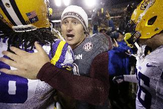 Texas A&M quarterback Johnny Manziel hugs LSU players after an NCAA college football game in Baton Rouge, La., Saturday, Nov. 23, 2013. LSU won 34-10. (AP Photo/Gerald Herbert)