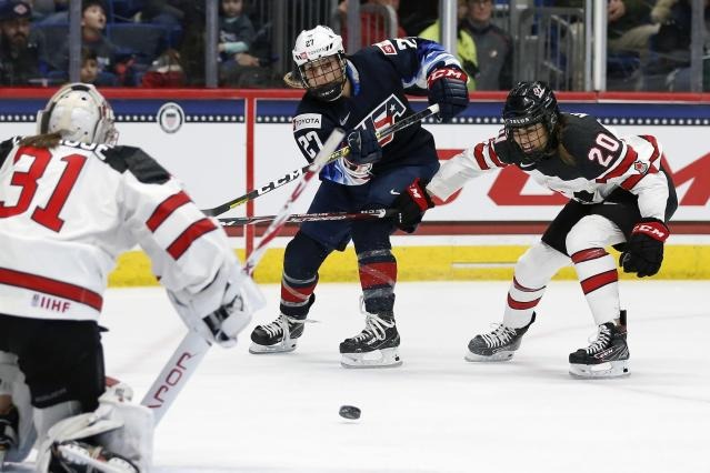 United States' Annie Pankowski (27) takes a shot on Canada's Geneviève Lacasse (31) as Sarah Nurse (20) defends during the first period of a rivalry series women's hockey game in Hartford, Conn., Saturday, Dec. 14, 2019. (AP Photo/Michael Dwyer)