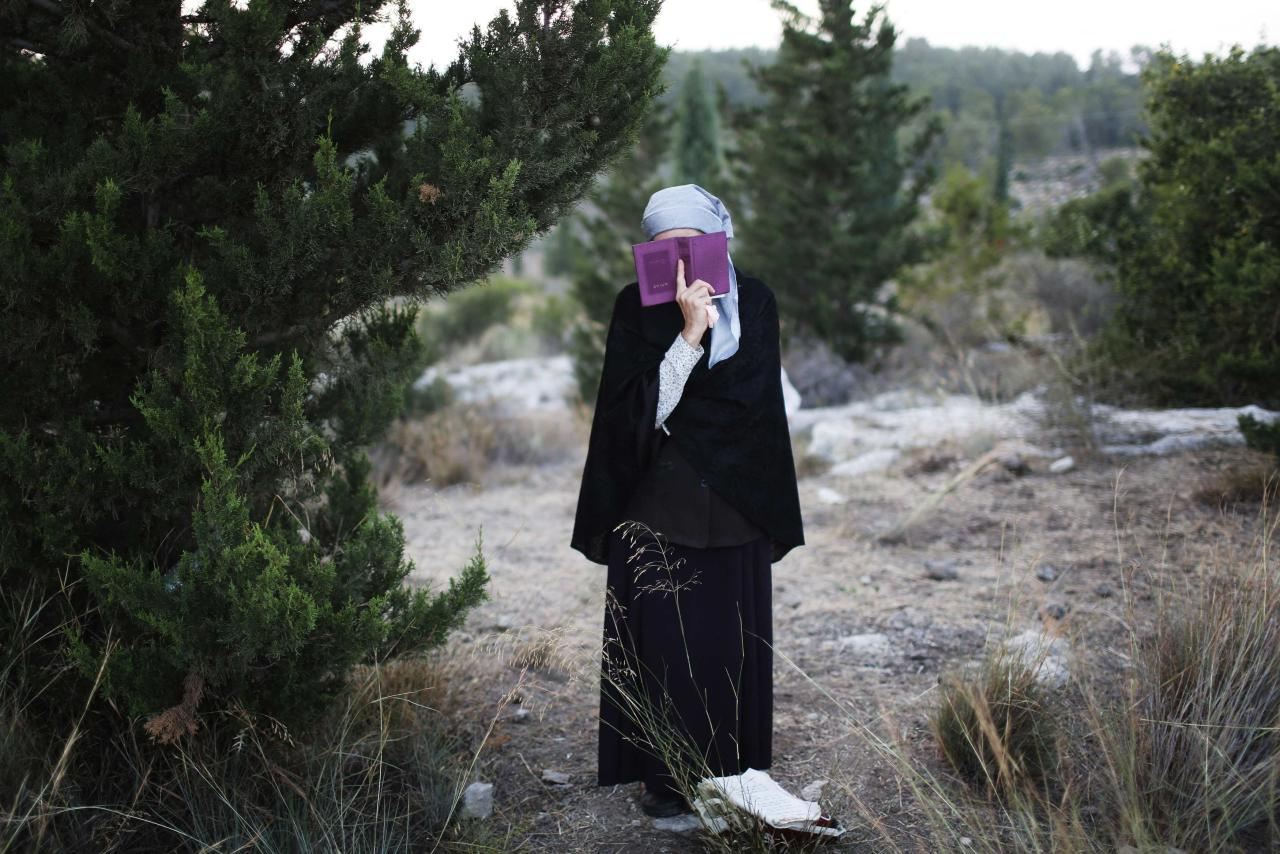 A Jewish woman prays during the joint funeral of the three Israeli teens who were abducted and killed in the occupied West Bank, in the Israeli city of Modi'in July 1, 2014. Tens of thousands of mourners joined in an outpouring of national grief on Tuesday at the burial of three Israeli teenagers, Gil-Ad Shaer, U.S.-Israeli national Naftali Fraenkel, both 16, and Eyal Yifrah, 19, whose kidnapping and killing Israel blamed on the Palestinian Islamist group Hamas. The Islamist group has neither confirmed nor denied involvement in the disappearance of the students as they hitchhiked near a Jewish settlement on June 12 nor in the cross-border rocket salvoes from Gaza. REUTERS/Finbarr O'Reilly (ISRAEL - Tags: POLITICS CIVIL UNREST RELIGION TPX IMAGES OF THE DAY)