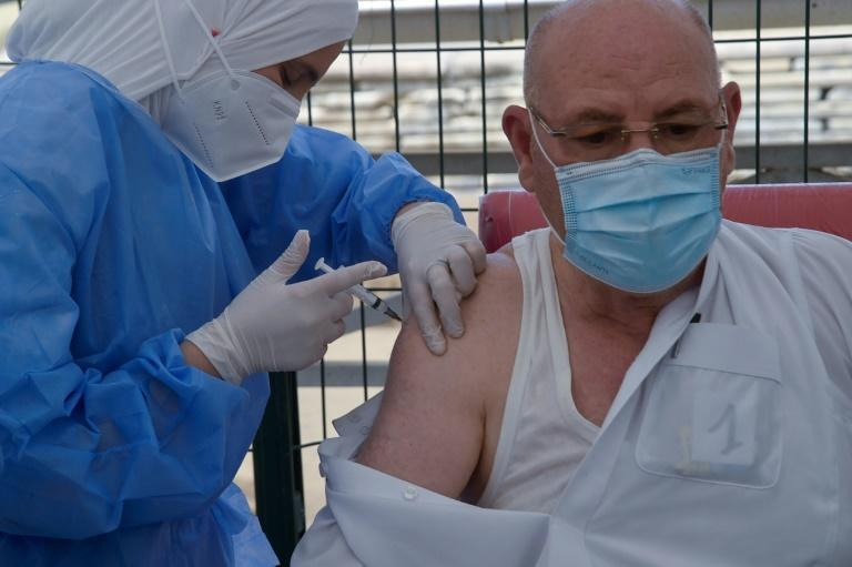 An Algerian medic administers a COVID-19 vaccine dose in front of the El-Kebir mosque in the capital Algiers
