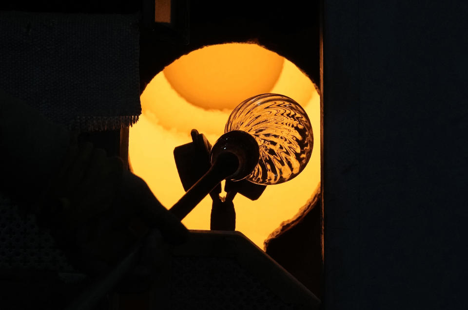 A glass-worker heats a glass artistic creation in a methane powered oven in Murano island, Venice, Italy, Thursday, Oct. 7, 2021. The glassblowers of Murano have survived plagues and pandemics and have transitioned to highly prized artistic creations to outrun competition from Asia, but surging energy prices may be their doom. (AP Photo/Antonio Calanni)