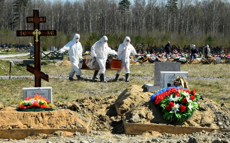 Workers wearing protective gear bury a coronavirus victim at a cemetery on the outskirts of Saint Petersburg
