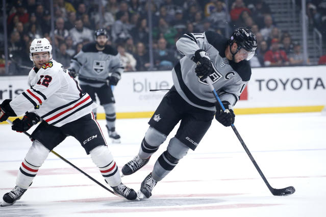 Los Angeles Kings forward Anze Kopitar, right, controls the puck away from Chicago Blackhawks forward Alex DeBrincat during the second period of an NHL hockey game Saturday, Nov. 2, 2019, in Los Angeles. (AP Photo/Ringo H.W. Chiu)