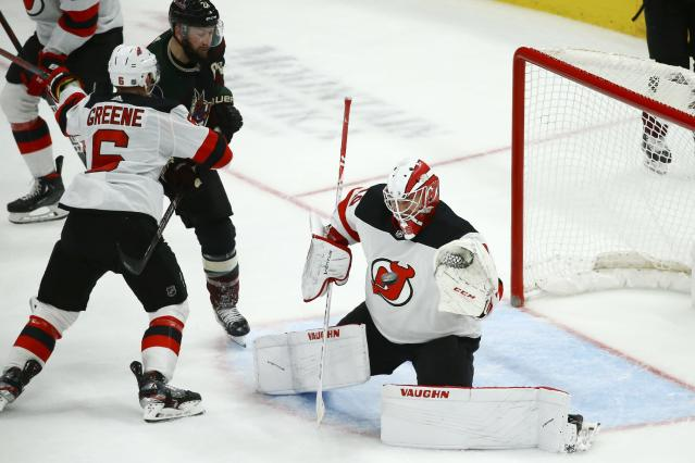 New Jersey Devils goaltender Mackenzie Blackwood, right, reaches out to make a glove save as Devils defenseman Andy Greene (6) pressures Arizona Coyotes center Derek Stepan (21) during the third period of an NHL hockey game, Saturday, Dec. 14, 2019, in Glendale, Ariz. The Devils defeated the Coyotes 2-1. (AP Photo/Ross D. Franklin)