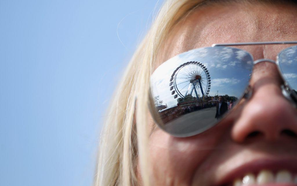 The giant ferris wheel is reflected in the glasses of a young woman at the Oktoberfest.