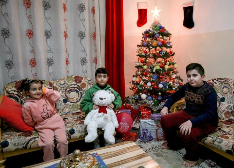 Ameel Saeed's children sit by a small Christmas tree at the home in Jordan, which has hosted waves of Iraqi refugees starting with the 1990 first Gulf War, the 2003 US-led invasion of Iraq and the 2014 emergence of the Islamic State jihadist group