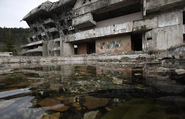 """In this picture taken on Friday, Feb. 21, 2014, graffiti by London creative collective The Lurkers """"The Lurkers do Sarajevo"""" is written on a destroyed hotel at Mt. Igman. Wartime destruction and negligence have turned most of Sarajevo's 1984 Winter Olympic venues into painful reminders of the city's golden times. The world came together in the former Yugoslavia in 1984 after the West had boycotted the 1980 Olympics in Moscow and Russia boycotted the 1984 Summer Games in Los Angeles. Just eight years later, the bobsleigh and luge track on Mount Trbevic was turned into an artillery position from which Bosnian Serbs pounded the city for almost four years. Today, the abandoned concrete construction looks like a skeleton littered with graffiti. (AP Photo/Amel Emric)"""