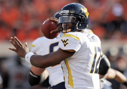 West Virginia quarterback Geno Smith looks for an open receiver during the first half of an NCAA college football game against Oklahoma State in Stillwater, Okla., Saturday, Nov. 10, 2012.(AP Photo/Brody Schmidt)