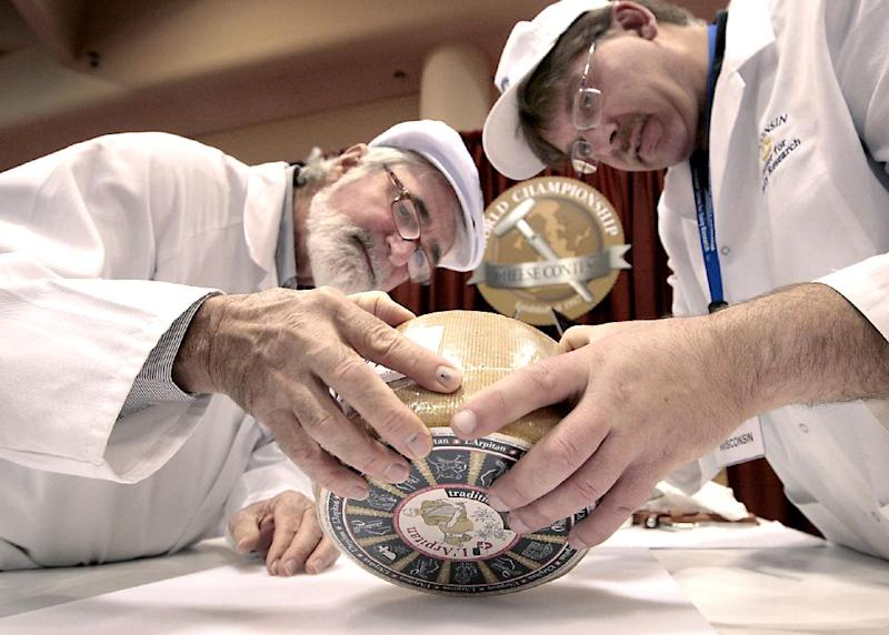 Russell Smith of Australia, left, and John Jaeggi of Madison prepare to sample one of the entries in the Smear Ripened Semi-soft Cheese category during the opening day of the World Championship Cheese Contest at the Monona Terrace Convention Center in Madison, Wis. on Monday, March 5, 2012. More than 2,500 entries will be judged throughout the three day gathering, sponsored every two years by the Wisconsin Cheese Makers Association. (AP Photo/Wisconsin State Journal, John Hart )