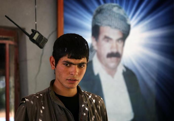 A member of the Kurdistan Workers' Party (PKK) poses in front of a portrait of jailed Kurdish rebel chief Abdullah Ocalan at the PKK headquarters in northern Iraq, on July 29, 2015 (AFP Photo/Safin Hamed)