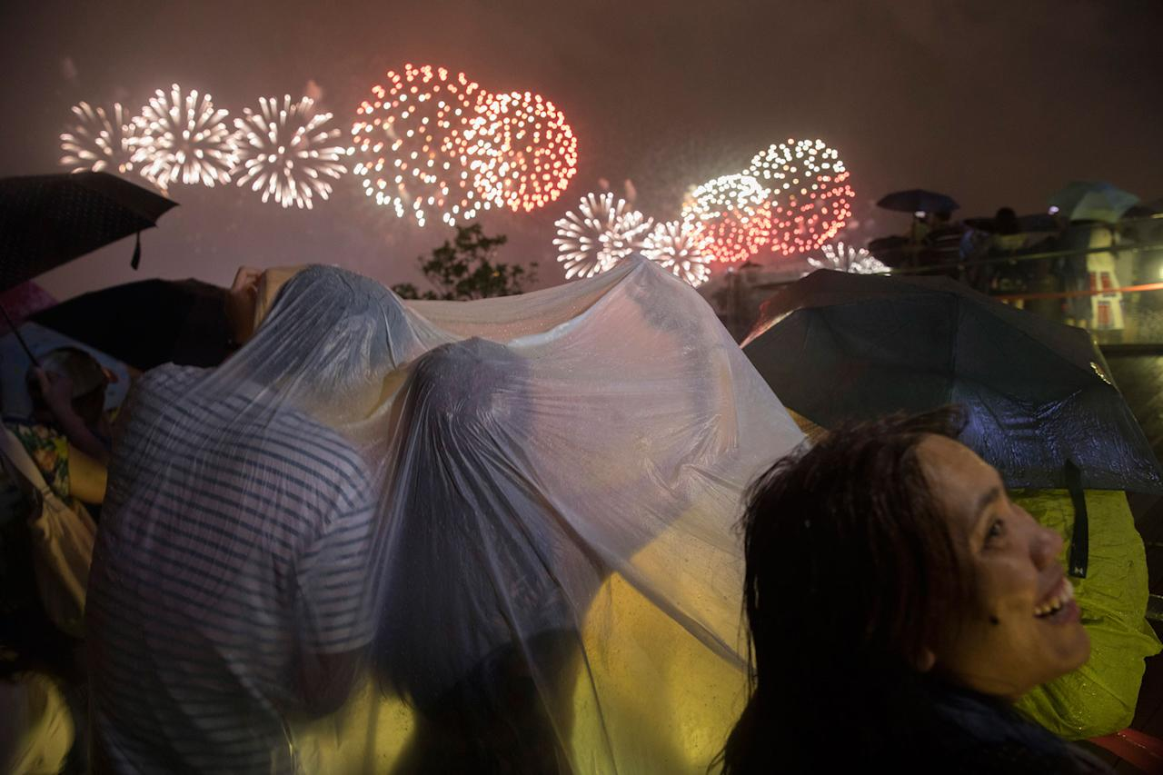 <p>A couple braves heavy rain to watch fireworks set off to mark the 20th anniversary of the Hong Kong handover to China in Hong Kong, Saturday, July 1, 2017. (Photo: Ng Han Guan/AP) </p>