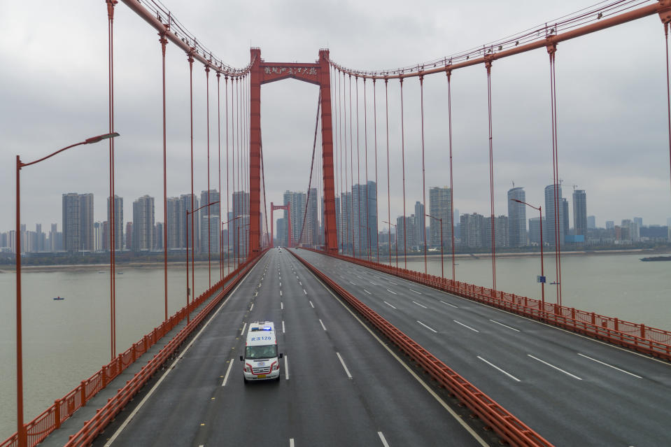 FILE - In this Saturday, Jan. 25, 2020, file photo, an ambulance drives across a nearly empty bridge in Wuhan in central China's Hubei Province. A 10-member team of international researchers from the World Health Organization hopes to find clues as to the origin of the coronavirus pandemic in the central Chinese city of Wuhan where the virus was first detected in late 2019. (Chinatopix via AP, File)