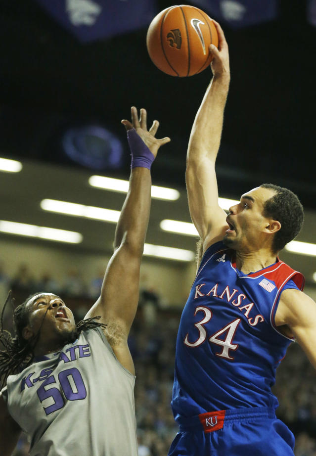 Kansas forward Perry Ellis (34) tries to dunk over Kansas State forward D.J. Johnson (50) during the first half of an NCAA college basketball game in Manhattan, Kan., Monday, Feb. 10, 2014. (AP Photo/Orlin Wagner)