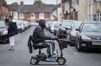 A man wearing a protective visor crosses the road on a mobility scooter, England, Monday June 29, 2020. The British government is reimposing lockdown restrictions in the central England city of Leicester after a spike in coronavirus infections, including the closure of shops that don't sell essential goods and schools. (Joe Giddens/PA via AP)