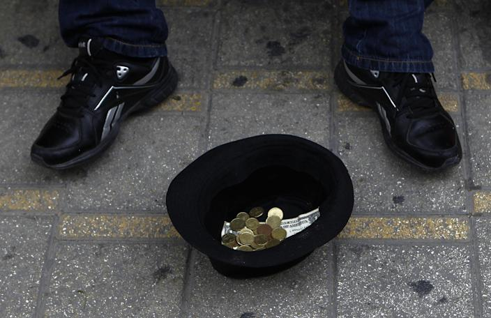 A hat with money belonging to a musician, is seen on the ground as he plays music at the main shopping street in central capital Nicosia, Cyprus, on Saturday, March 30, 2013. Big depositors at Cyprus' largest bank may be forced to accept losses of up to 60 percent, far more than initially estimated under the European rescue package to save the country from bankruptcy, officials said Saturday. (AP Photo/Petros Karadjias)