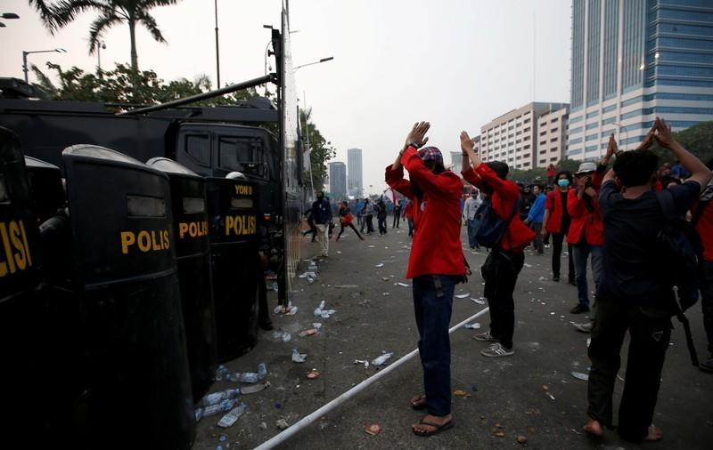 FILE PHOTO: University students gesture in front of police officers as they protest outside the Indonesian Parliament in Jakarta